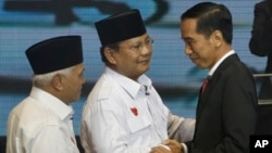 Indonesian presidential candidates Joko Widodo, right, Prabowo Subianto, center, and Subianto's running mate Hatta Rajasa greet each other during a televised debate in Jakarta, June 9, 2014