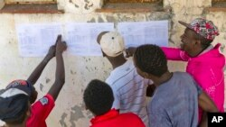Zimbabweans check the results posted outside a polling station in Bulawayo, Zimbabwe, July 31, 2018.