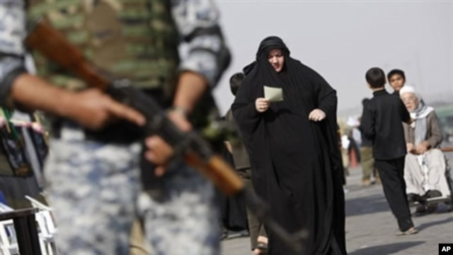 An Iraqi soldier stands guard as Muslim Shiite pilgrims pass through Baghdad on their way to the holy city of Karbala to mark the Shiite mourning day of Arbaeen, 01 Feb 2010