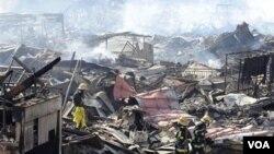 Tim SAR Jepang mencari korban di antara reruntuhan di Kesennuma, Senin (14/3).