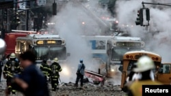 Emergency workers respond as steam and smoke from the center of 41st street at the scene of an explosion...