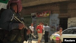 Fleeing civilians walk past a member of the Free Syrian Army in Aleppo's district of Salah Edinne July 31, 2012.
