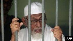Giáo sĩ cực đoan Abu Bakar Bashir nói chuyện với các phóng viên từ sau song sắt của nhà tù của một tòa án ở Jakarta, Indonesia, ngày 9/5/2011