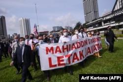 Anggota parlemen oposisi Malaysia Anwar Ibrahim (tengah) dan lainnya berbaris di parlemen saat mereka memprotes penutupannya di Kuala Lumpur pada 2 Agustus 2021. (Foto: AFP/Arif Kartono)
