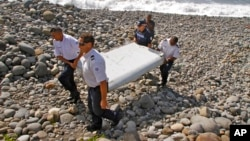 FILE - French police officers carry a piece of debris, the first trace of Malaysia Airlines Flight 370, in Saint-Andre, Reunion Island.