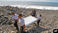 French police officers carry a piece of debris, the first trace of Malaysia Airlines Flight 370, in Saint-Andre, Reunion Island, July 29, 2015.