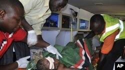12月25日尼日利亚首都阿布贾一天主教会发生爆炸后,医护人员在急救车内照料一位受害者