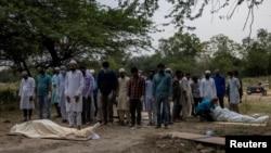 Warga Muslim India melakukan shalat jenazah korban COVID-19 sebelum dimakamkan di New Delhi (foto: Reuters).
