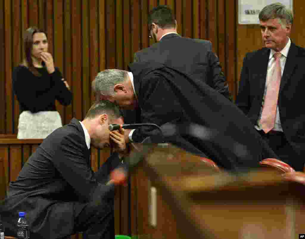 A crying Oscar Pistorius, left, is comforted by his defense lawyer, Barry Roux, during the third day of sentencing hearings in the high court in Pretoria, South Africa.