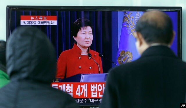 FILE - People watch a live broadcast of South Korean President Park Geun-hye's press conference, at the Seoul Railway Station in Seoul, South Korea, Jan. 13, 2016. Park called for resumption of nuclear talks, even if Pyongyang does not participate.
