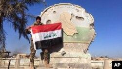 28일 이라크 정부군이 이슬람 수니파 무장조직 ISIL로부터 서부 거점도시 라마디를 탈환한 후 정부 시설에서 이라크 국기를 펼쳐보이고 있다.