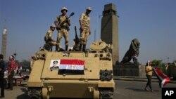 Tentara Mesir berjaga di atas kendaraan lapis baja, untuk mengamankan wilayah di sekitar jembatan menuju Lapangan Tahrir di Kairo, Mesir, Jumat (26/7).