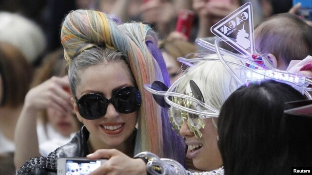 Singer Lady Gaga poses for a photograph with a fan upon her arrival at Narita international airport in Narita, east of Tokyo May 8, 2012.