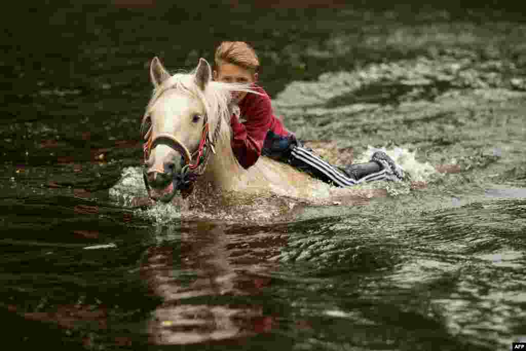 A youth washes a horse in the River Eden on the second day of the annual Appleby Horse Fair, in the town of Appleby-in-Westmorland, northwest England.
