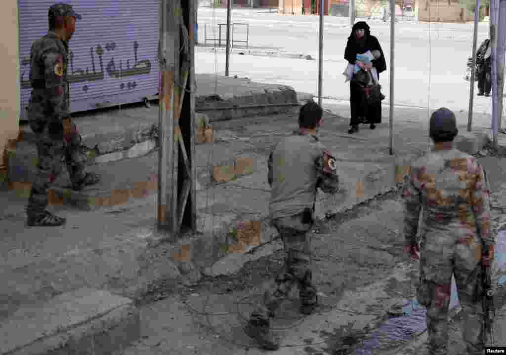 A woman holds her child as she crosses from a part of Mosul controlled by Islamic State fighters into an area n Mosul run by Iraqi special forces soldiers.