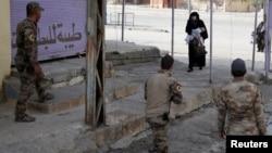 Një grua me fëmijën duke ikur nga zona e kontrolluar nga ISIS-i në Mosul në pjesën e kontrolluar nga ushtria irakiane