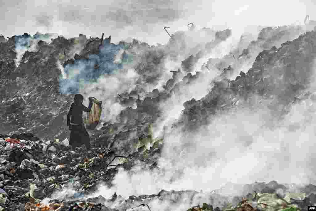 A boy sifts through a garbage dump near an oil field in the countryside of Malikiya in northeast Syria.