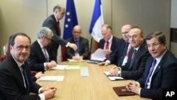 Presiden Perancis Francois Hollande (kiri) dan para pejabat Uni Eropa mencapai kesepakatan dengan delegasi Turki yang dipimpin PM Ahmet Davutoglu di Brussels, Belgia hari Jumat (18/3).