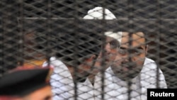 FILE - Political activists Ahmed Maher, Ahmed Douma (L) and Mohamed Adel (R) of the 6 April movement look on from behind bars in Abdeen court in Cairo, December 22, 2013. Three leading Egyptian activists were sentenced to three years in prison each.
