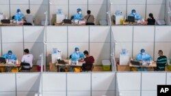 In this photo released by China's Xinhua News Agency, people get COVID-19 vaccinations at a vaccination site at a sports arena in Nanjing in eastern China's Jiangsu Province, Monday, Aug. 2, 2021. (Li Bo/Xinhua via AP)