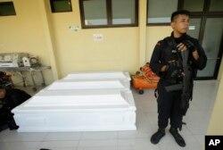Seorang petugas polisi berjaga-jaga dekat peti mati yang dipersiapkan untuk korban serangan gereja di sebuah rumah sakit di Surabaya, Indonesia, Senin, 14 Mei 2018. (Foto: dok).