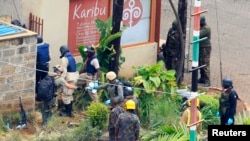 Foreign experts, flanked by military personnel, check the walls around the Westgate shopping mall in Nairobi, Sept. 25, 2013.