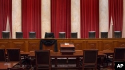 This photo provided by the Collection of the Supreme Court of the United States shows the Courtroom of the Supreme Court showing Associate Justice Antonin Scalia's Bench Chair draped in black, Tuesday, Feb. 16, 2016, at the court in Washington. (Franz Jantzen/Collection of the Supreme Court of the United States via AP)