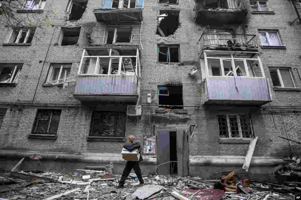A man carries his belongings from an apartment building damaged from shelling in Slovyansk, eastern Ukraine, June 12, 2014.