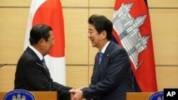 Japanese Prime Minister Shinzo Abe, right, and Cambodia's Prime Minister Hun Sen shake hands after their meeting at Abe's office in Tokyo Monday, Oct. 8, 2018. (AP Photo/Eugene Hoshiko, Pool)