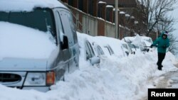 Peter Gonsiorowski works to shovel out his car following a winter blizzard in Somerville, Massachusetts, Jan. 28, 2015.
