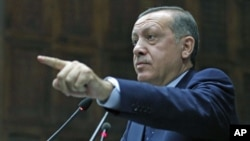 Turkey's Prime Minister Tayyip Erdogan addresses members of parliament from his ruling AK Party during a meeting at the Turkish parliament in Ankara, Turkey, October 11, 2011.