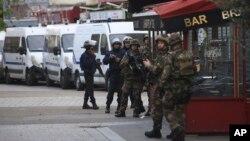 프랑스 경찰이 18일 파리 북부 외곽 생드니에서 테러 용의자들의 은신처를 급습한 가운데, 현장 주변에 경찰 특부수대원과 군인들이 서있다.