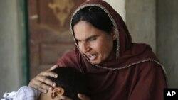 در این عکس که اردیبهشت ماه گرفته شده، «کوثر پروین» سعی دارد فرزند خود را که قربانی جنسی ملاها شده، آرام کند.