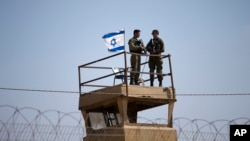 FILE - Israeli soldiers stand guard atop a watch tower along the Israel-Gaza Strip border, May 15, 2018.