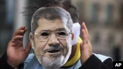Người biểu tình đeo mặt nạ Tổng thống Ai Cập Mohammed Morsi trong cuộc biểu tình tại Berlin, Đức, ngày 30/1/2013.
