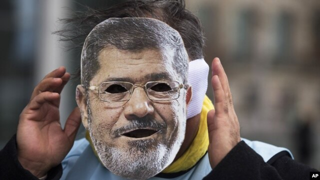 A man covers his face with a mask of Egypt President Mohamed Morsi during a protest in front of the chancellery against the visit of Morsi prior to a meeting of him with German Chancellor Angela Merkel in Berlin, Germany, January 30, 2013.