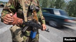 An armed pro-Russian separatist with attached orange ribbon of St. George, a symbol widely associated with pro-Russian protests in Ukraine, stands guard at a road checkpoint outside the eastern Ukrainian city of Luhansk, June 8, 2014.