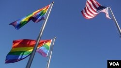 FILE - A U.S. and LGBT flags are seen fluttering in and undated photo in West Hollywood, California. Insults and bullying directed against students of non-traditional sexual orientations are common and teachers don't intervene to stop them, Human Rights Watch reports.