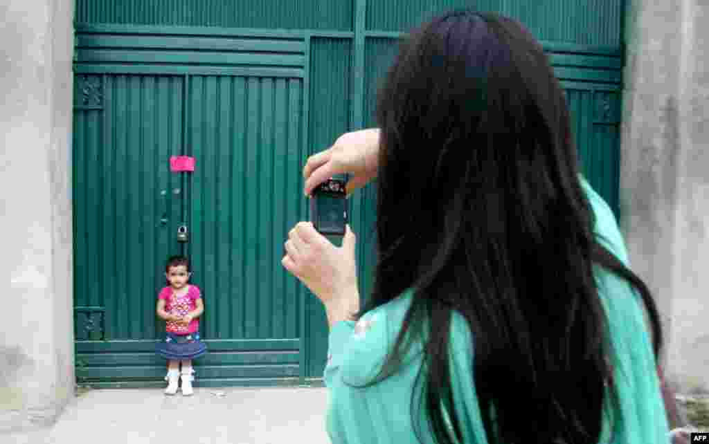 May 5: A woman photographs her daughter at a gate of the compound where Osama bin Laden was caught and killed in Abbottabad, Pakistan. (AP Photo/Aqeel Ahmed)