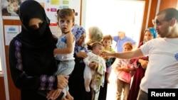 敘利亞婦女及兒童6月11日在邊境地方等候醫療照顧。