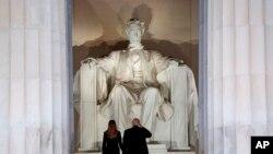 """El presidente electo Donald Trump y su esposa, Melania Trump, saludan el monumento del Lincoln Memorial, al llegar la noche anterior a su posesión como presidente de EE.UU., al """"Make America Great Again Welcome Concert""""."""