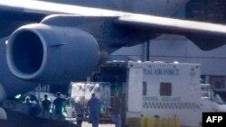 Nhân viên y tế chuyển một nữ nhân viên y tế người Anh từ phi cơ xuống xe cấp cứu tại Không lực Northolt ở mạn tây London, 12/3/15