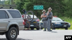 Polisi negara bagian New York menjaga penghalang jalan yang dipasang dekat jalan layang di dekat kota Malone, di tengah pencarian napi buron (27/6). (AFPScott Olson/Getty Images)
