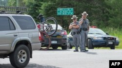 New York State Police officers man a roadblock along Highway 30 near Malone, New York, as the manhunt for escaped convict David Sweat continues, June 27, 2015.