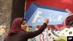 Mahasiswi Mesir melukis mural bergambar logo Facebook. (Foto: Dok)