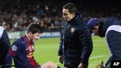 Lionel Messi, penyerang klub Barcelona asal Argentina, ditandu akibat cedera lutut ketika bertabrakan dengan kiper dalam pertandingan Liga Champions melawan klub Benfica (foto, 5/12/2012)..
