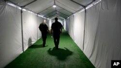 ARCHIVO - En esta fotografía de archivo del 2 de mayo de 2019, dos agentes de la Patrulla Fronteriza recorren un pasillo en un centro de detención en Donna, Texas. (AP Foto/Eric Gay, Archivo)