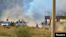 Smoke rises during clashes between irregular forces loyal to former Libyan army chief of staff General Khalifa Hafter and Islamist militants, in the eastern city of Benghazi, June 2, 2014.