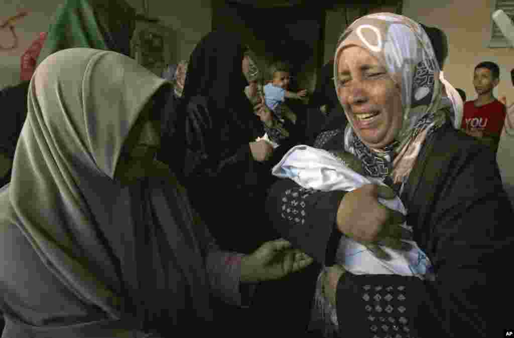 A relative holds a dead baby during the funeral of members of Al Ghoul family in the Rafah refugee camp, in the southern Gaza Strip. At least 40 people were inside the Al Ghoul family building in Rafah when it was targeted by Israeli jet fighters, according to the Red Crescent and Gaza health official Ashraf al-Kidra.