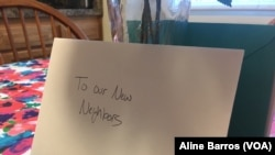 """A """"Welcome new neighbors"""" card sits on a kitchen table in a three-story townhouse in Columbia, Maryland. The house is ready for the arrival of a refugee family. (A. Barros/VOA)"""